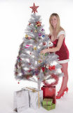 Woman in Santa costume decorating a Christmas tree Royalty Free Stock Images