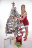 Woman in Santa costume decorating a Christmas tree Royalty Free Stock Photography