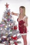 Woman in Santa costume decorating a Christmas tree Royalty Free Stock Image