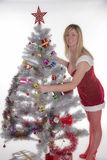 Woman in Santa costume decorating a Christmas tree Stock Image