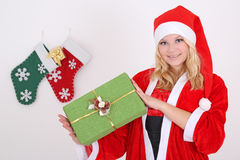 Woman in santa costume with gift Stock Photos