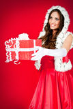 Woman in santa costume giving a present Stock Images