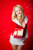 Woman in Santa costume giving present Royalty Free Stock Photography