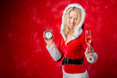 Woman in Santa costume holding clock and glass of campaign Royalty Free Stock Photos