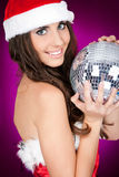 Woman in santa costume holding disco ball Stock Images