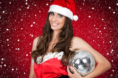 Woman in santa costume holding disco ball Stock Photo