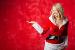 Woman in Santa costume holding her hand out Royalty Free Stock Images