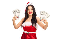 Woman in Santa costume holding money Stock Photo