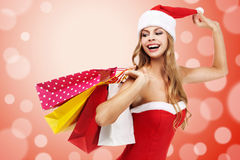 Woman in santa costume holding a shopping bags Stock Photo