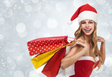Woman in santa costume holding a shopping bags Stock Image