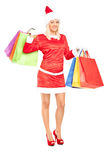 Woman in Santa costume holding shopping bags. Full length portrait of a woman in Santa costume holding shopping bags isolated on white background Royalty Free Stock Photography