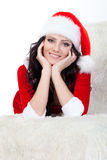 Woman in santa costume laying on sofa Royalty Free Stock Image