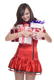 Woman in santa dress with gifts. Emotional playful woman  in santa claus dress, white fur and some gifts Royalty Free Stock Images