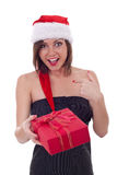 Woman in Santa dress holding a present Royalty Free Stock Photography