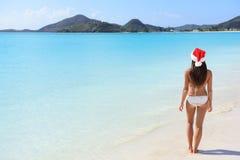 Woman in Santa hat on beach travel vacation. Getaway enjoying view of tropical beach turquoise paradise beach in the Caribbean. Beautiful girl in bikini under Stock Photos