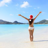 Woman In Santa Hat And Bikini on Beach Christmas. Woman standing in water with arms outstretched at beach. Rear view of female is wearing Santa hat and bikini Royalty Free Stock Images