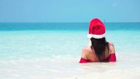 Woman in santa hat in bikini at tropical beach. Slow motion. Woman in santa`s hat in bikini at tropical beach stock footage