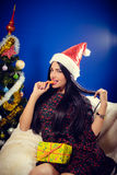Woman in Santa hat biting mandarin beside Royalty Free Stock Images