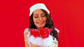 Woman in Santa hat blowing Xmas snowflake. stock video footage