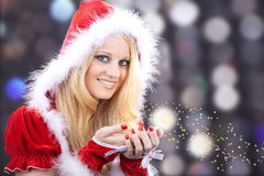 Woman with santa hat blows the stars Royalty Free Stock Photo