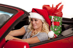 Woman santa hat car gift drive. A woman sitting in her car driving down the road in her Santa hat with a present in her back seat Stock Photos