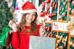 Woman In Santa Hat Carrying Shopping Bags. Portrait of happy young woman in Santa hat carrying shopping bags at store Stock Photography