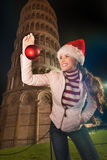 Woman in Santa hat with Christmas ball near Leaning Tower, Pisa Stock Images