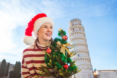 Woman in Santa hat with Christmas tree near Leaning Tour, Pisa Royalty Free Stock Images