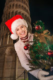 Woman in Santa hat with Christmas tree near Leaning Tower, Pisa Royalty Free Stock Photography