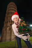 Woman in Santa hat with Christmas tree near Leaning Tower, Pisa. The iconic Italian architecture adds style to the Christmas celebration. Portrait of merry young Royalty Free Stock Photo