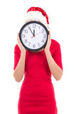 Woman in santa hat with clock posing isolated on white Stock Photo