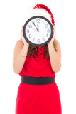 Woman in santa hat with clock posing isolated on white Stock Photos