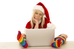 Woman in Santa hat and colored socks with laptop sad Royalty Free Stock Photography