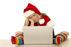 Woman in santa hat and colored socks with laptop sleeping Royalty Free Stock Photo