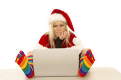 Woman in Santa hat and colored socks with laptop thinking Stock Photos