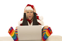 Woman in Santa hat and colorful socks laptop hands on head. A woman with a shocked expression on her face with her Santa gear on Royalty Free Stock Image