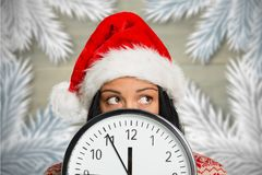 Woman in santa hat covering her face behind clock Royalty Free Stock Photography