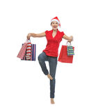 Woman in Santa hat dancing with shopping bags Royalty Free Stock Images