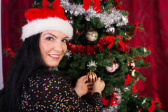 Woman with santa hat decorates tree Royalty Free Stock Images