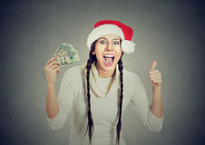 Woman in santa hat with dollar bills showing thumb up. Happy young smiling woman in santa helper red hat with dollar bills showing thumb up, isolated on gray royalty free stock photo