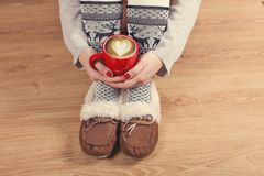 Close-up of female legs in warm socks with a deer, christmas presents, wrapping paper, decoration and cup of cappuccino top view. Stock Image
