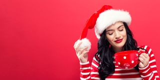 Woman with Santa hat drinking coffee. Happy young woman with Santa hat drinking coffee Royalty Free Stock Photography