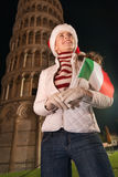 Woman in Santa hat with flag looking up near Leaning Tower, Pisa Stock Photo