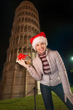 Woman in Santa hat with gift box near Leaning Tower of Pisa Stock Photography