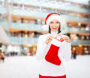 Woman in santa hat with gift box and stocking Stock Images