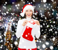 Woman in santa hat with gift box and stocking Royalty Free Stock Images