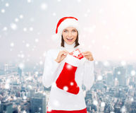 Woman in santa hat with gift box and stocking Royalty Free Stock Photography