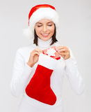 Woman in santa hat with gift box and stocking Stock Image