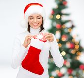 Woman in santa hat with gift box and stocking Stock Photos