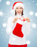 Woman in santa hat with gift box and stocking Royalty Free Stock Image